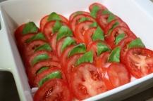 Arrange tomato slices and insert basil leaves.