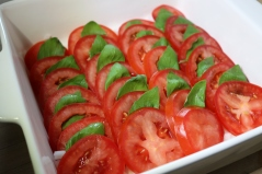Arrange tomato slices and insert basil leaves.
